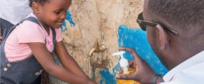 A Projects Abroad volunteer working with children in Kenya gives soap to a child washing their hands outdoors.